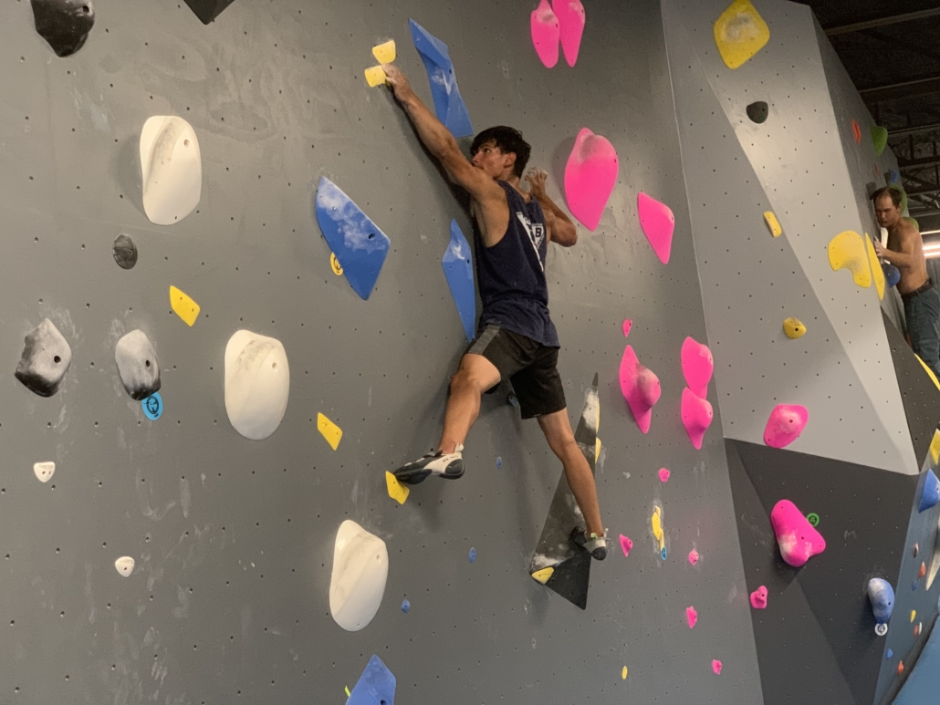 Climber stretching fingertips to small hold