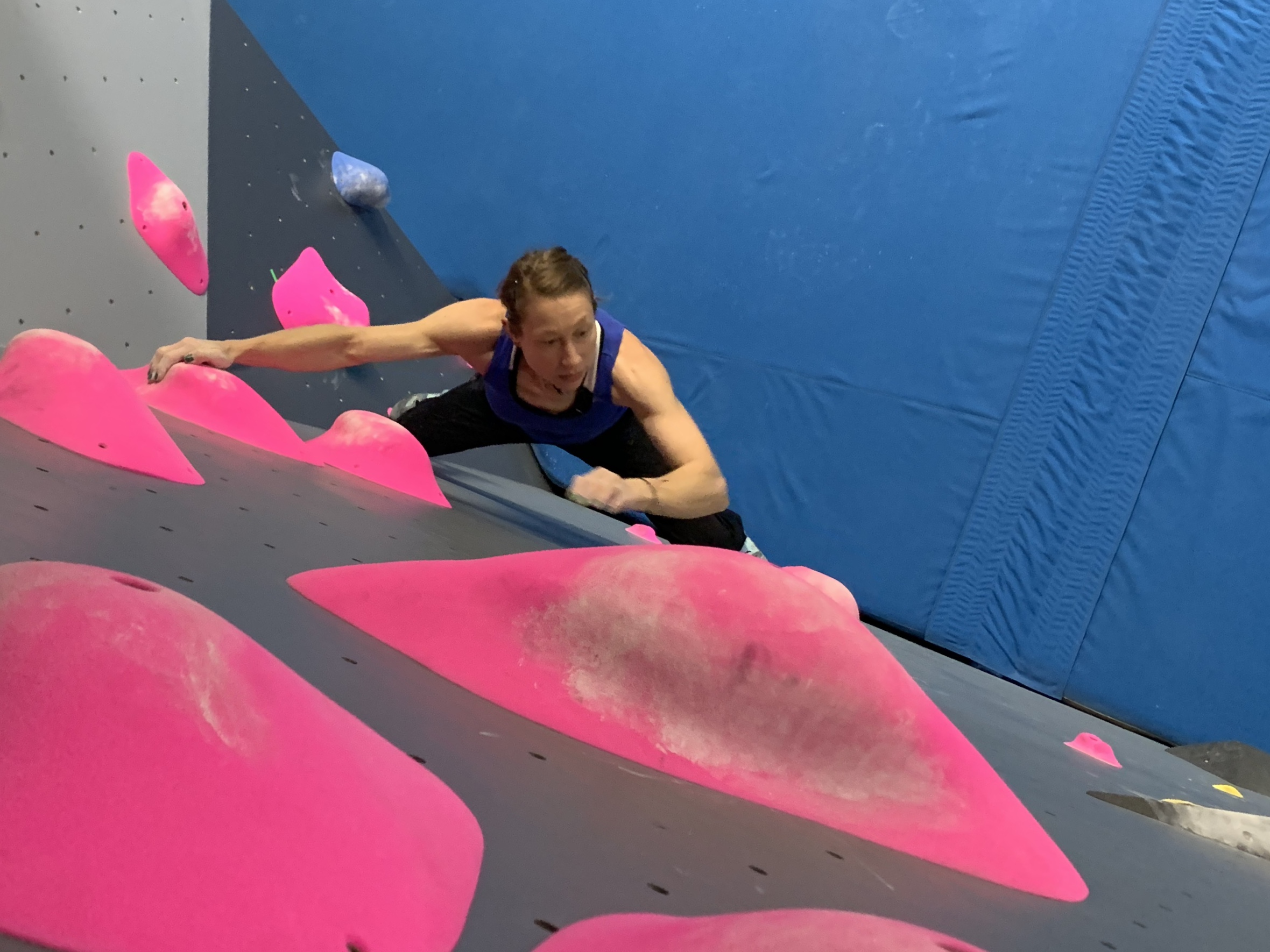 Woman with muscular shoulders climbing indoors