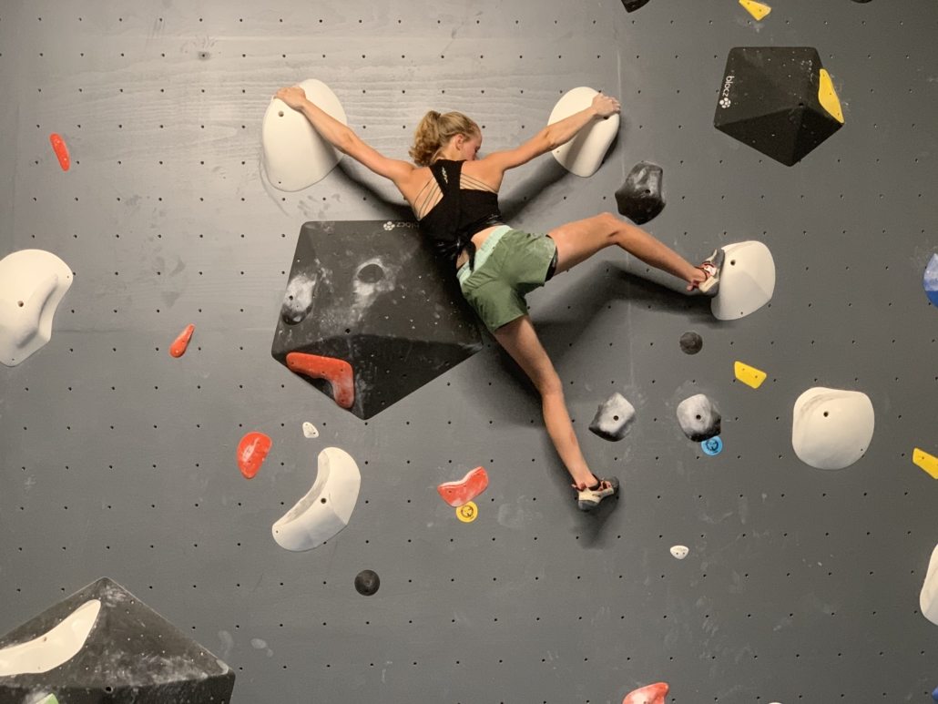 Fit woman, arms spanning wide on climb