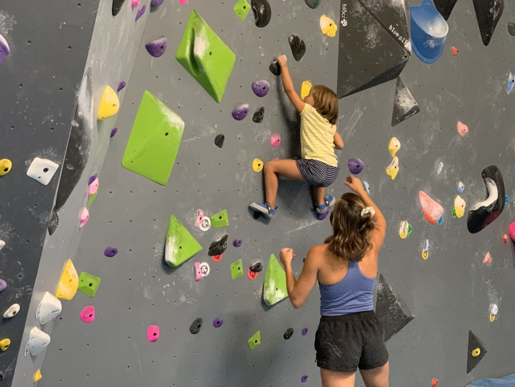 A young climber grabs a hold on climbing wall spotted by her coach