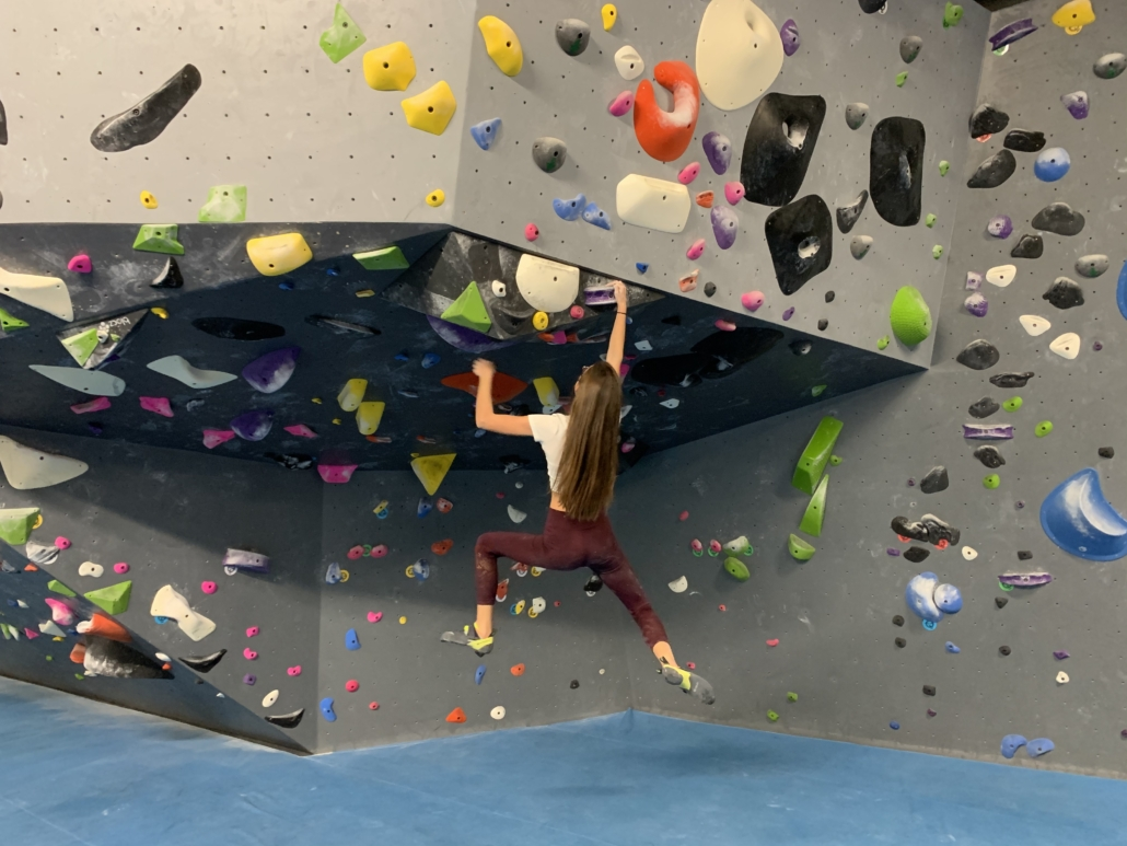 Girl swinging by one hand on the edge of the overhang