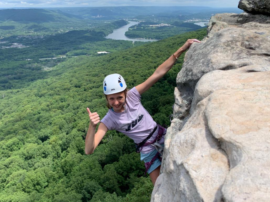 Climber gives thumbs-up at top of rock climb, Chattanooga